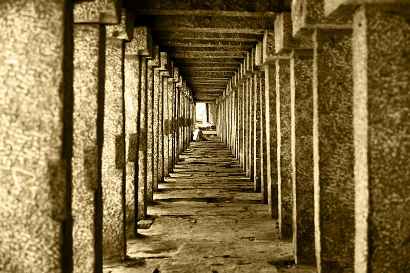 stone pillars temple repetition man sitting sepia